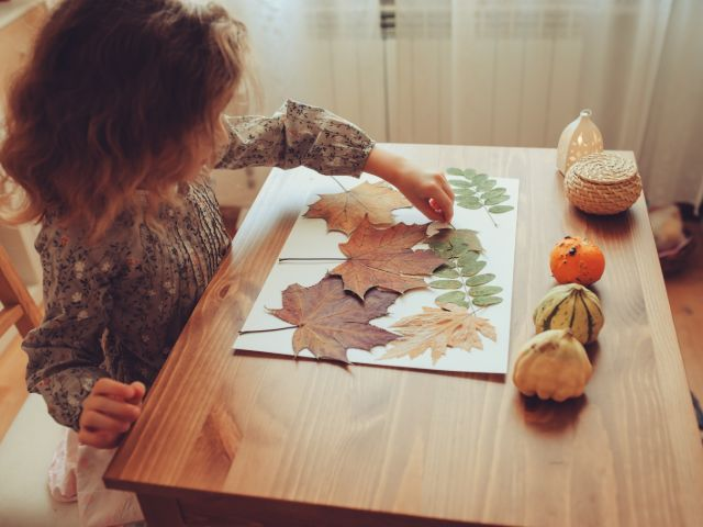 girl making art piece with leaves
