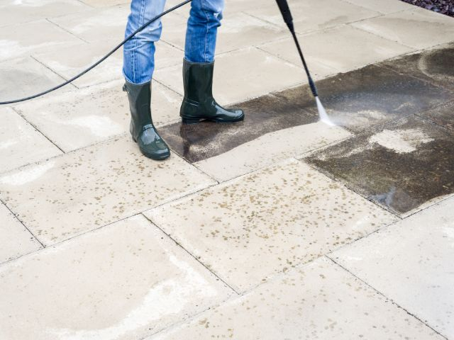 Person pressure cleaning patio